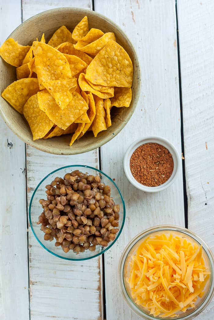 bowls of chips, lentils, cheese, and taco seasoning for making lentil nachos on a white board