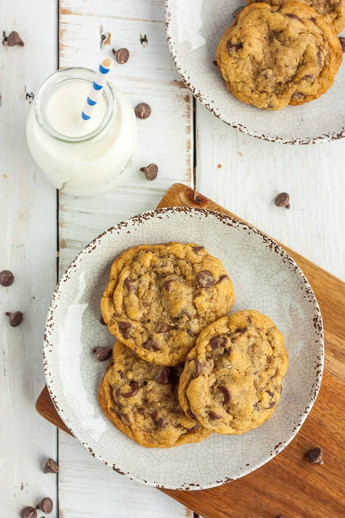 2 plates of chocolate chip cookies on a wooden board with a small bottle of milk that has a straw in it
