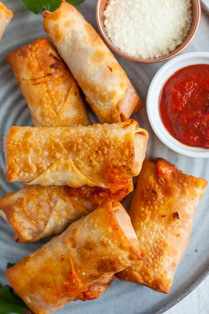 A stack of pizza rolls on a grey plate with a bowl of marinara and a bowl of parmesan cheese