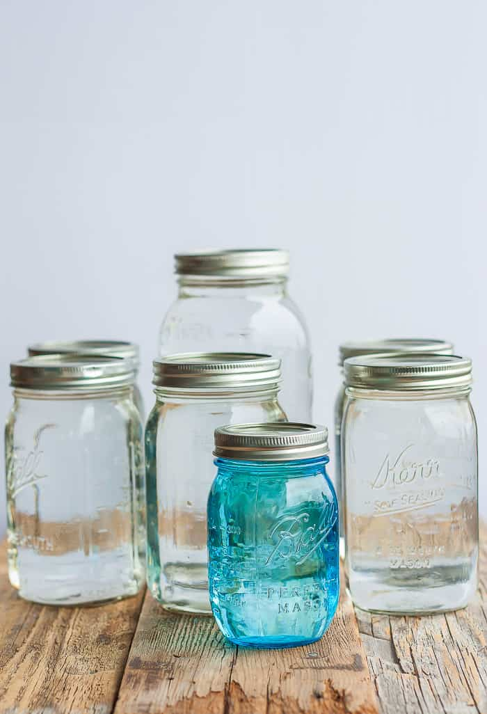 Canning jars of different sizes full of canned water on a wooden board