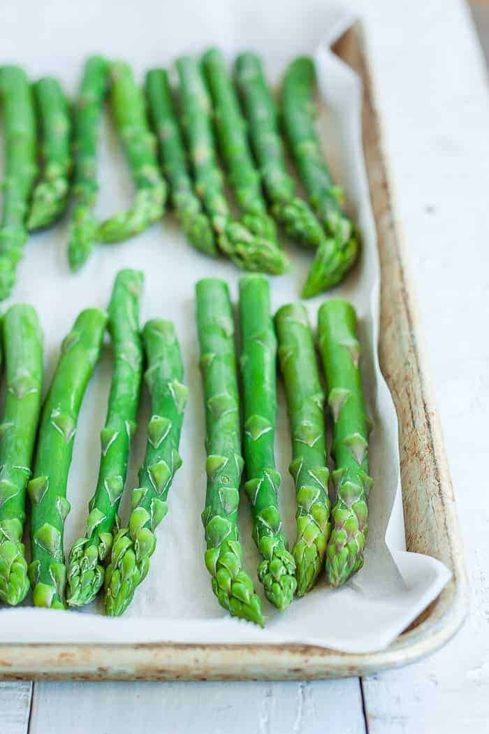A baking tray with frozen asparagus