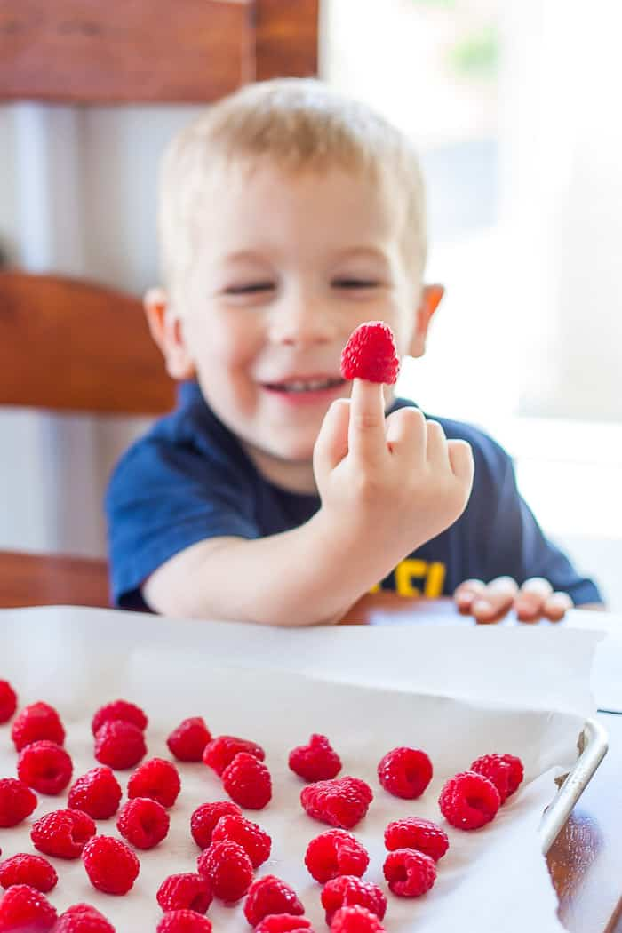 a smiling boy with a raspberry on his finger