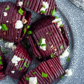 A grey plate with roasted beets topped with goat cheese, hazelbuts, and parsley