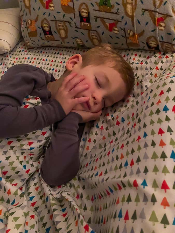 a boy sleeping with his hands on his face