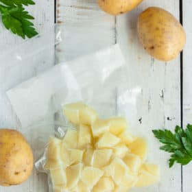 a bag of diced potatoes on a white board with whole potatoes and parsley