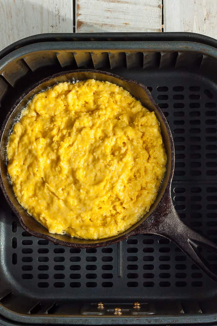 A small cast iron skillet with cornbread batter in an air fryer skillet