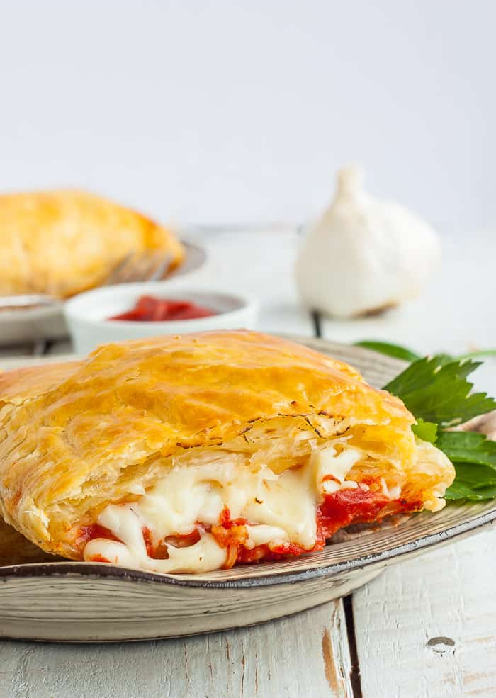 A pizza pocket cut in half with gooey mozzarella cheese