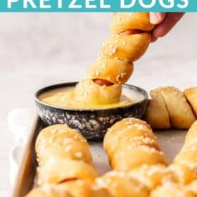 A hand dipping an air fryer pretzel dog into a bowl of mustard