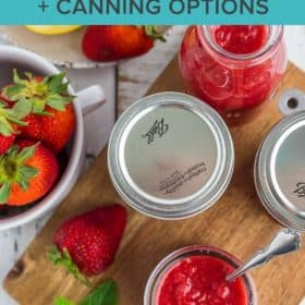 canning jars of strawberry syrup with lemons, fresh berries, and mint