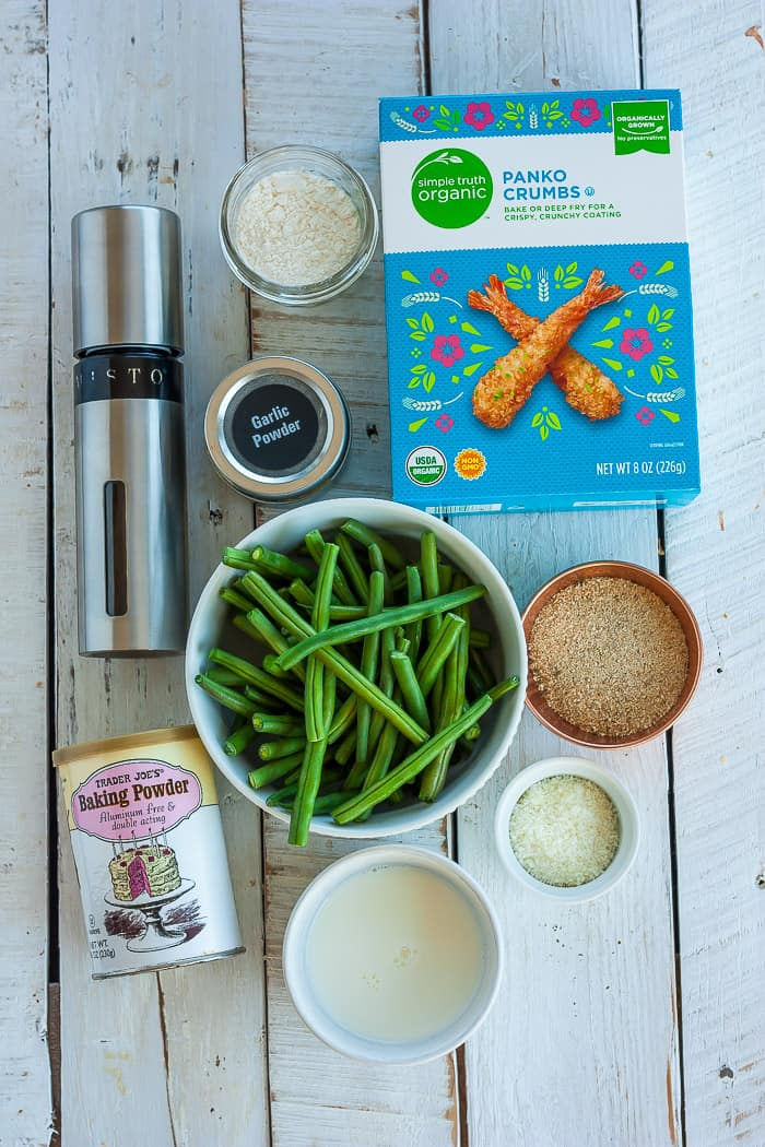 a bowl of green beans with breadcrumbs, herbs, and other ingredients for making crispy green bean fries