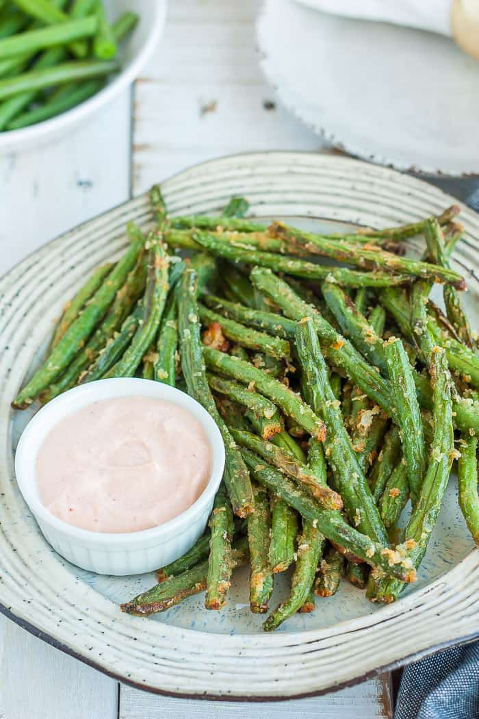 a plate of crispy green beans with a small dish of dressing