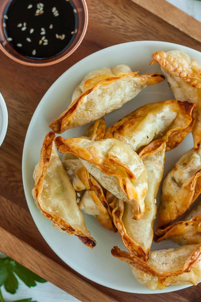A white plate with crispy air fryer potstickers and a small bowl of dipping sauce