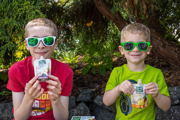 2 boys wearing sunglasses holding North Coast Organic fruit + veggie pouches