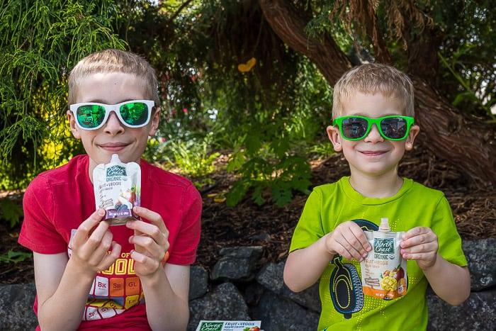 2 boys wearing sunglasses holding North Coast Organic fruit + veggie pouches
