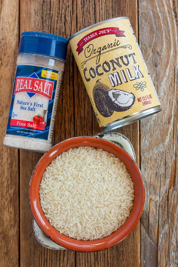 A bowl of rice, a shaker of salt, and a can of coconut milk on a wooden board