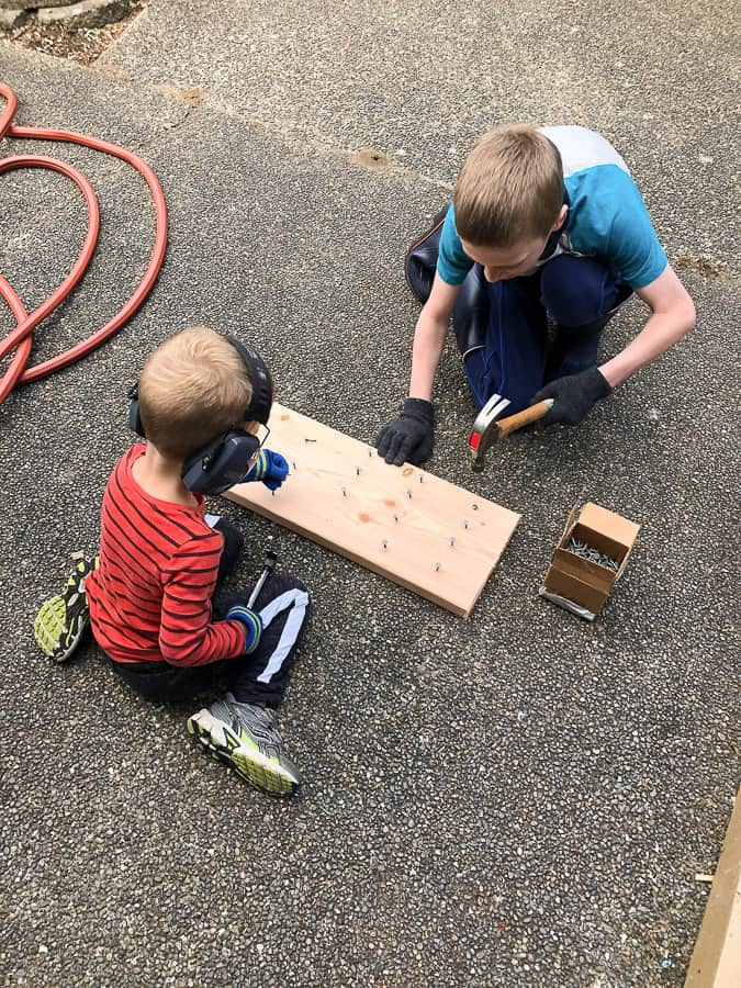 2 boys hammering nails into a board