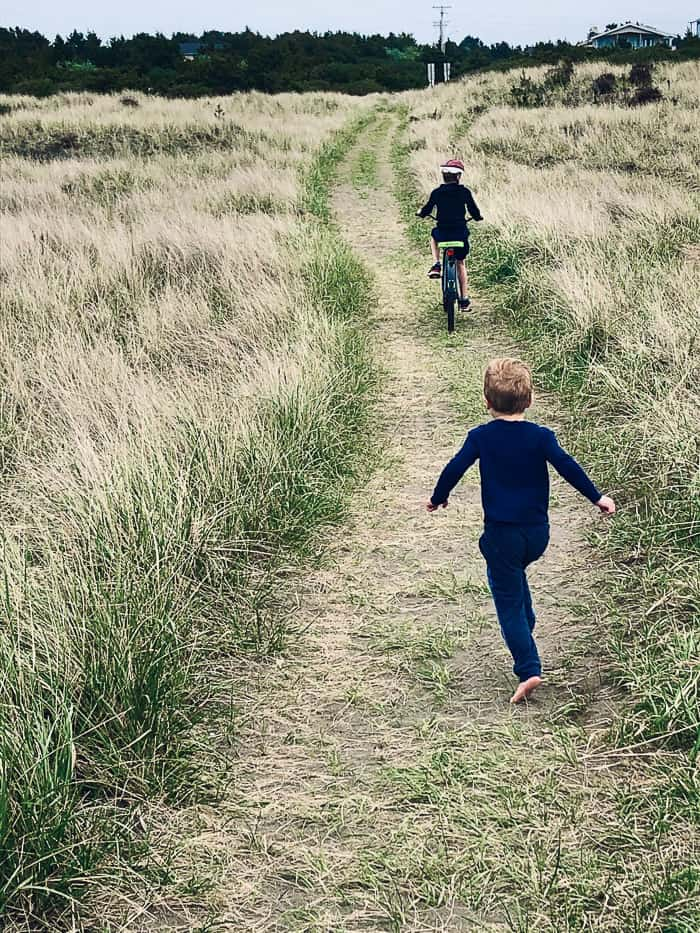 a child on a bike with another child running behind him through tall grass