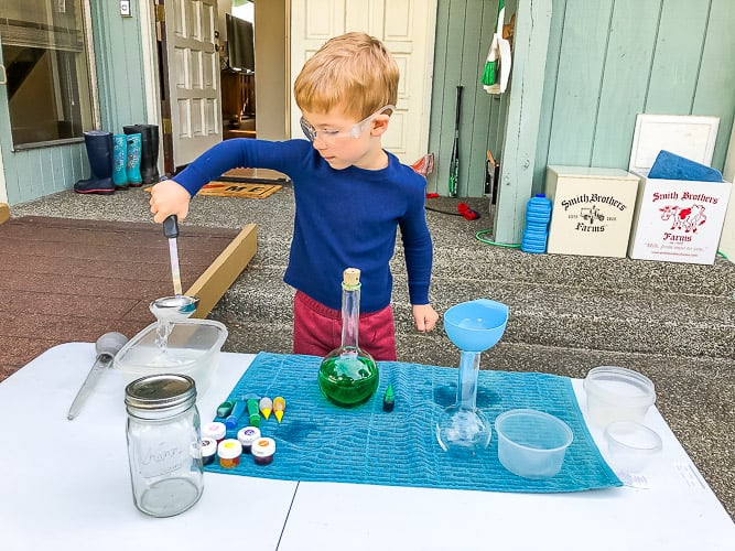 a child doing science experiments at a table outside