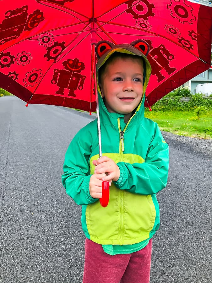 a small boy with an umbrella and rain coat