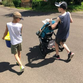3 boys walking down a hill, one in a stroller