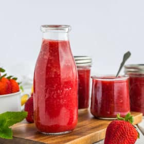 Mulitple glass jars of strawberry syrup on a wooden board with fresh strawberries and mint