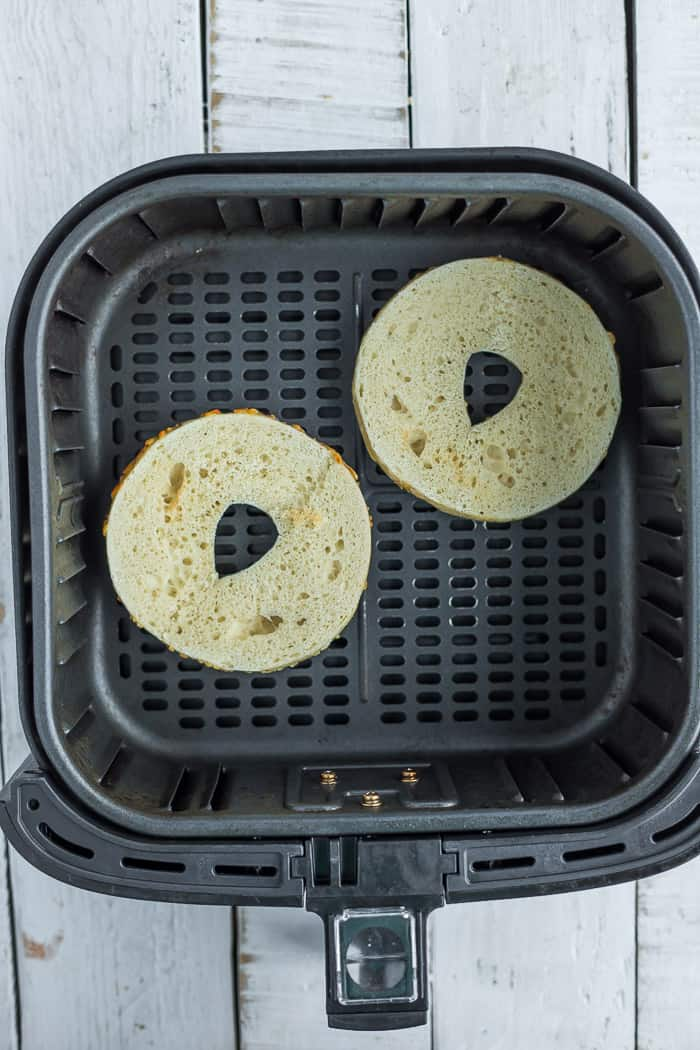 a sliced bagel in an air fryer basket