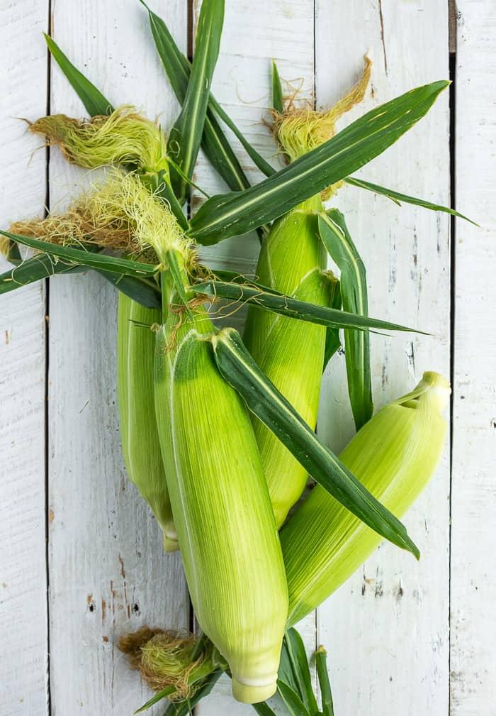 4 ears of corn on a white board