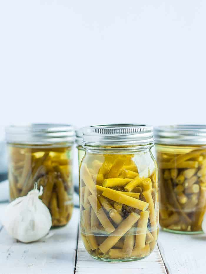 jars of green beans with a head of garlic on a white board