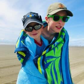 2 boys on a beach wrapped in a beach towel