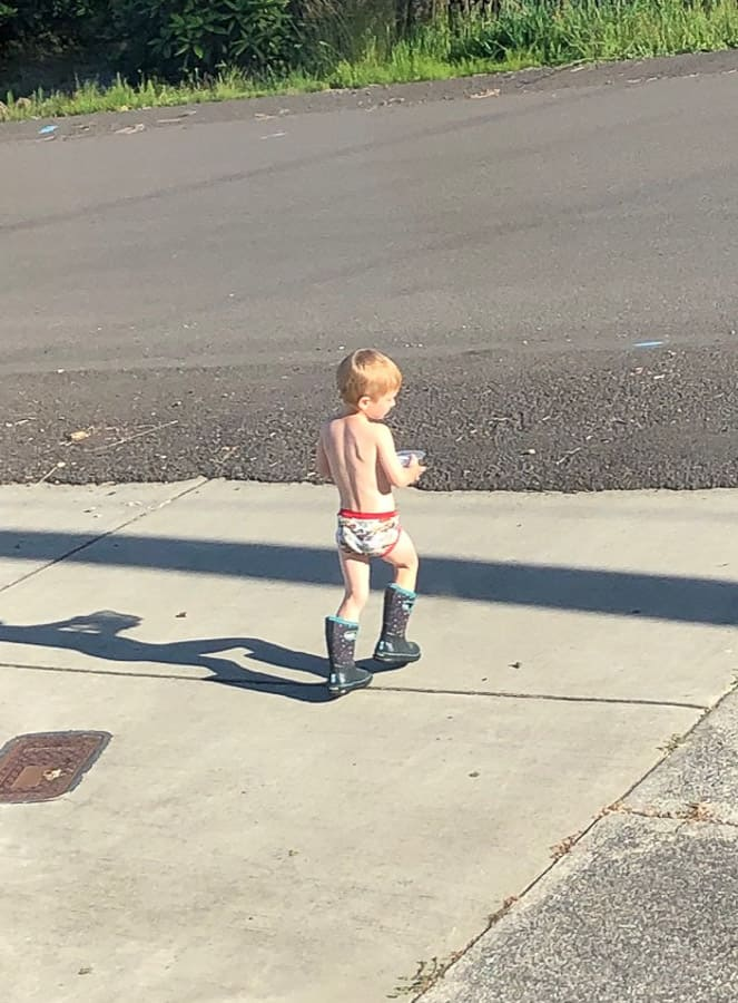 a boy in his underwear and boots on a road