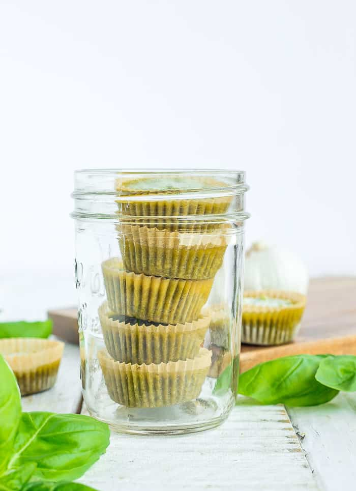 frozen cubes of pesto in a canning jar with basil on a white board