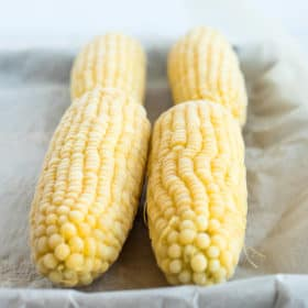 4 frozen ears of corn on a baking sheet