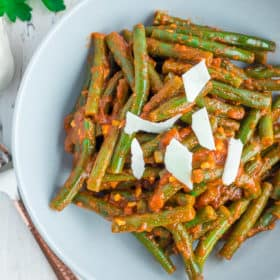 a grey bowl with green beans in tomato sauce topped with shaved parmesan