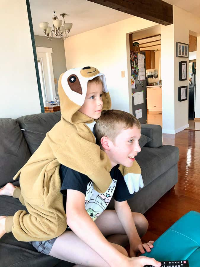 a boy in a sloth costume climbing on his brother