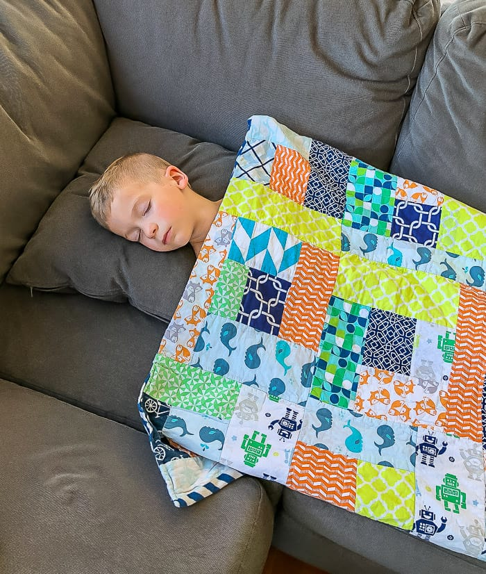 a boy sleeping on a couch covered by a colorful blanket