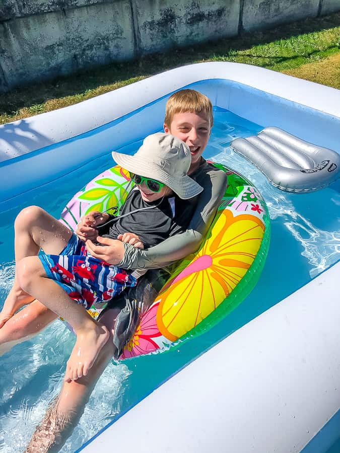 2 boys in a blow up swimming pool