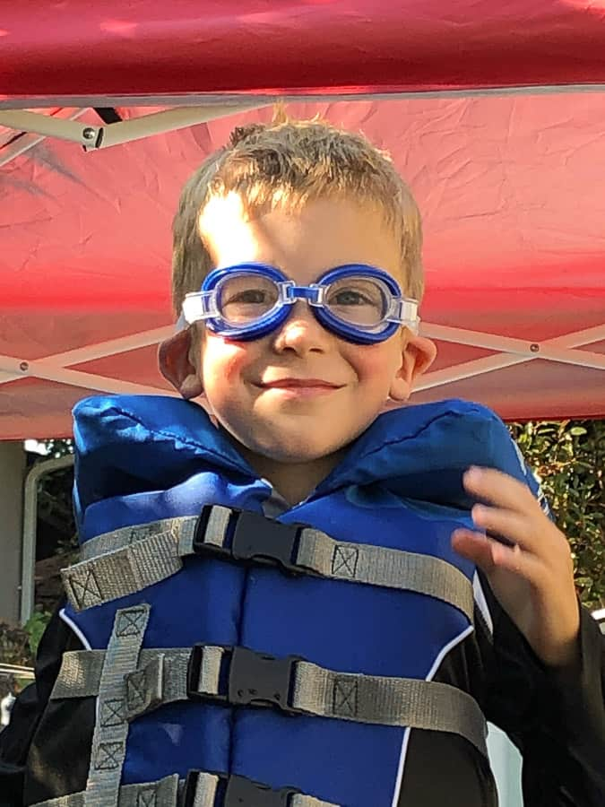a boy wearing goggles and a life jacket