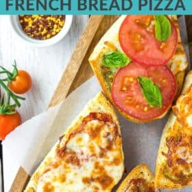 french bread pizzas on a wooden tray with tomatoes and other toppings on a white board
