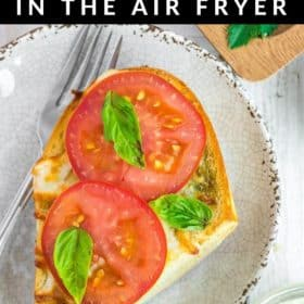 a piece of air fryer french bread pizza topped with fresh tomatoes and basil