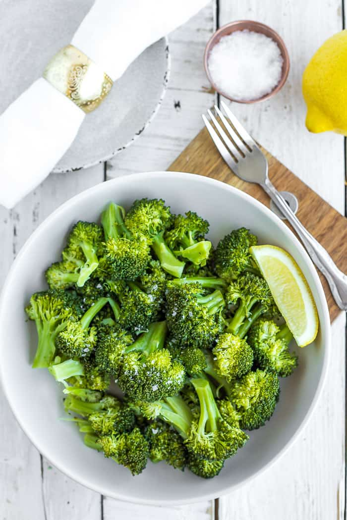 a white bowl of instant pot steamed broccoli on a wooden board with a fork and lemon wedge