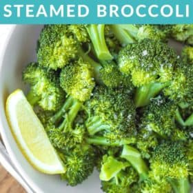 a bowl of green steamed broccoli with a lemon wedge