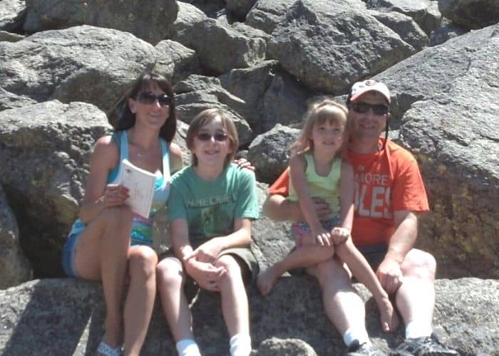 a family of four sitting in front of rocks
