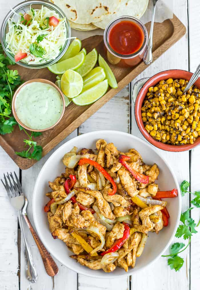 a white bowl with air fryer chicken fajitas, a tray of toppings, and a bowl of corn on a white board
