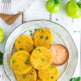 a plate of fried green tomatoes on a white board with small green tomatoes