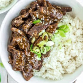 A white bowl of rice and Instant Pot teriyaki beef topped with green onions