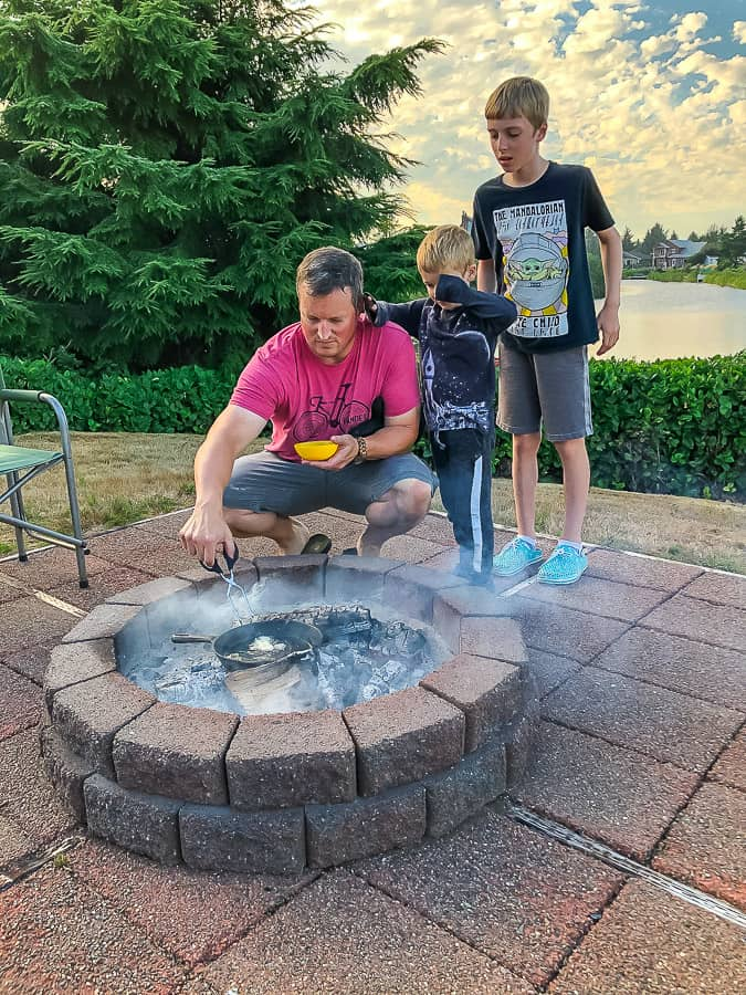 3 boys cooking a fish over a campfire