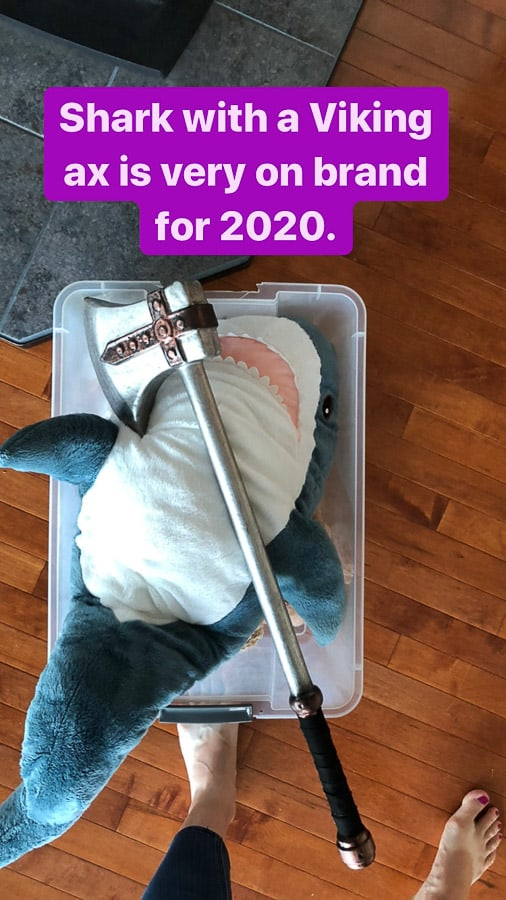 a stuffed shark in a plastic box with a toy ax