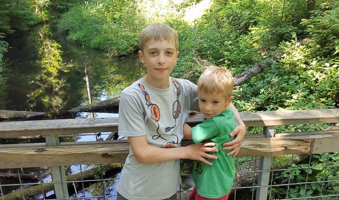 2 boys on a bridge at a park