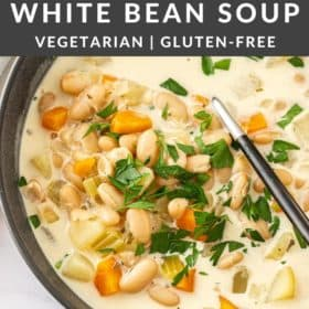 a black bowl with creamy white bean soup topped with parsley