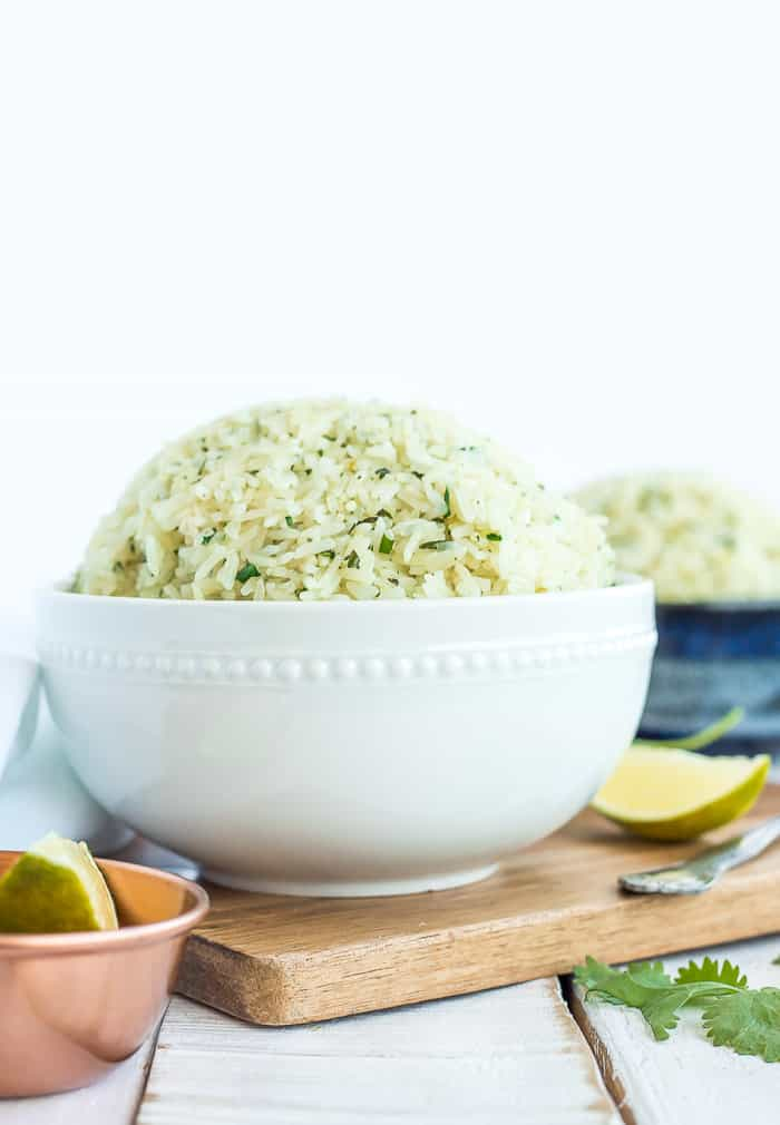 a white bowl of cilantro rice on a wooden board